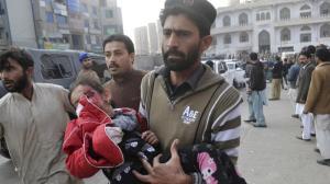 A man carrying an injured child. AP PHOTO
