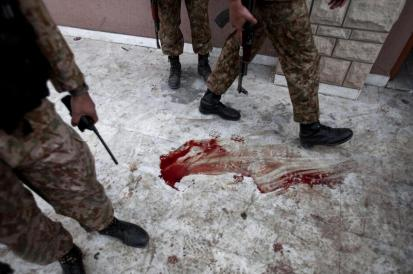 Pakistani troops walk over blood stained floor schools